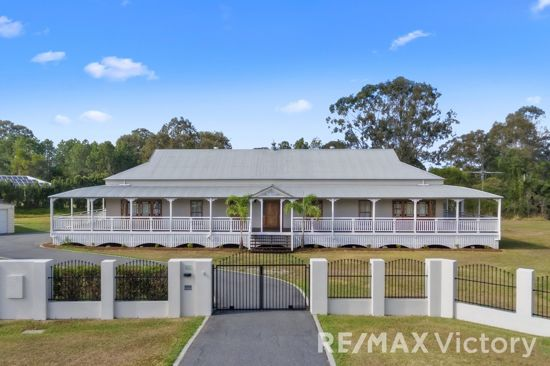 As you enter the street & approach electric gates to this beautifully renovated Queenslander, you will...
